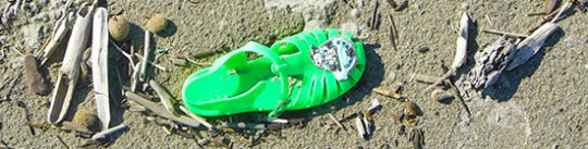 Plastiksandale grün im Sand
