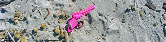 Spielzeugpistole Plastik pink im Sand