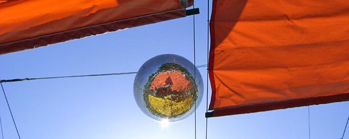 Discokugel draussen im Gegenlicht mit orangen Sonnenstoren