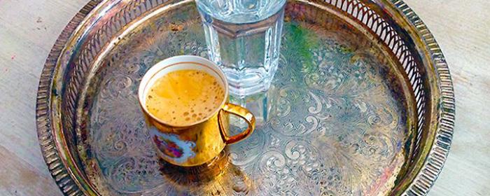 silbernes Tablett mit einer Tasse Kaffee und einem Glas Wasser